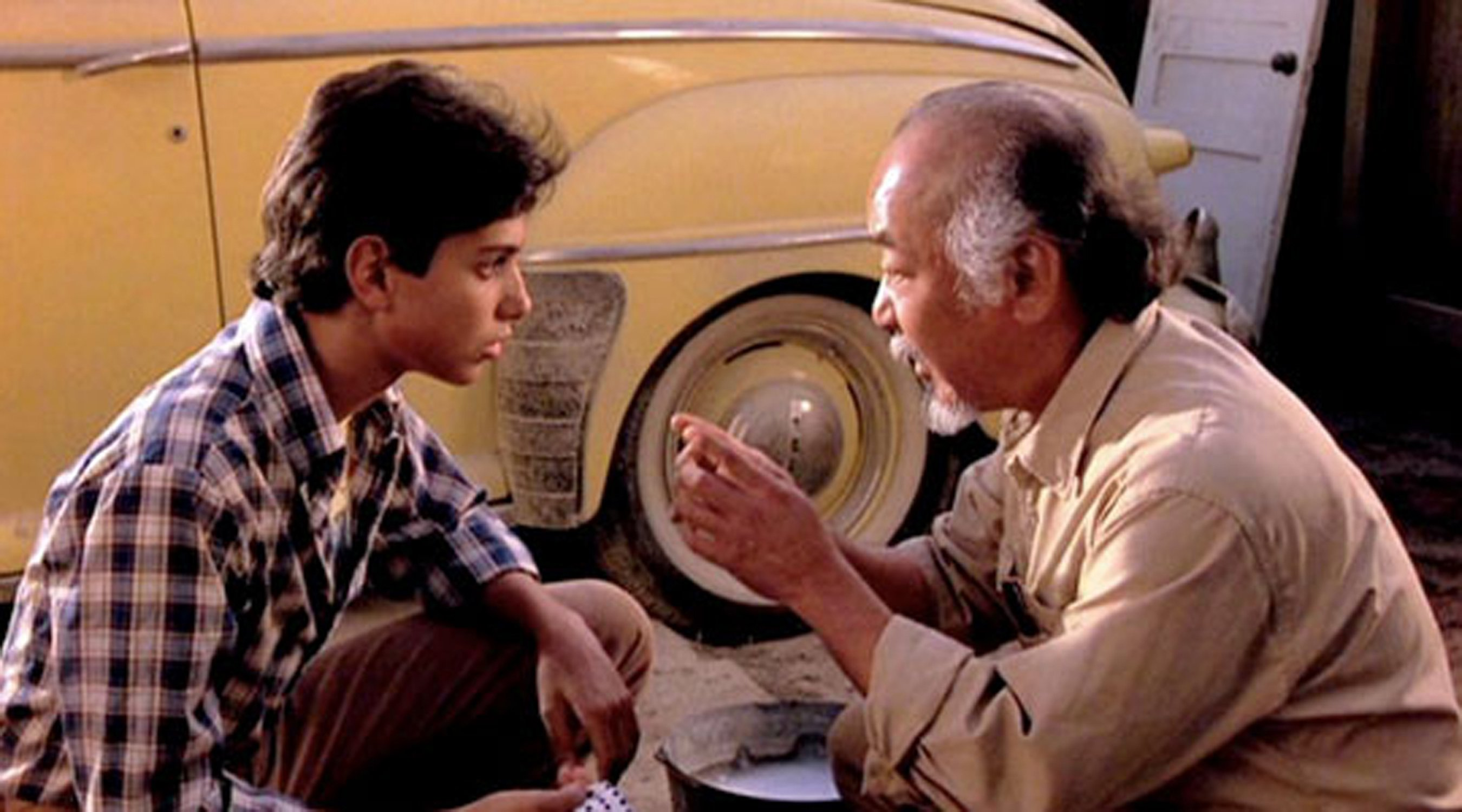Mr. Miyagi (Pat Morita) assigns Daniel (Ralph Macchio) to unrelated chores in The Karate Kid, 1984 (Columbia Pictures)
